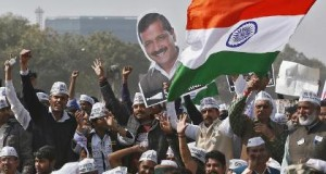 Supporters of Aam Aadmi (Common Man) Party (AAP) cheer as they hold an Indian national flag and a cutout of AAP chief Arvind Kejriwal, who took an oath as the new chief minister of Delhi, during a swearing-in ceremony at Ramlila ground in New Delhi February 14, 2015. The two-year-old anti-graft party took office in the Indian capital on Saturday, promising to fight divisive politics in a challenge to the federal government of Narendra Modi that has faced criticism for attacks on churches and other minorities. REUTERS/Anindito Mukherjee (INDIA - Tags: POLITICS)