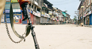 Srinagar: An armed CRPF jawan stands guard on a deserted road during curfew at Budshah Chowk in Srinagar on Tuesday. PTI Photo by S Irfan(PTI8_3_2010_000043B)